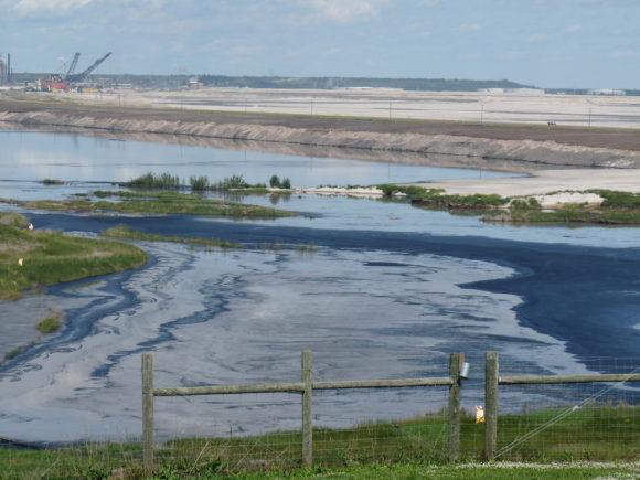 Abbau von Ölsand in Alberta, Kanada in der Syncrude Mine, Fort McMurray Öllache am Rand