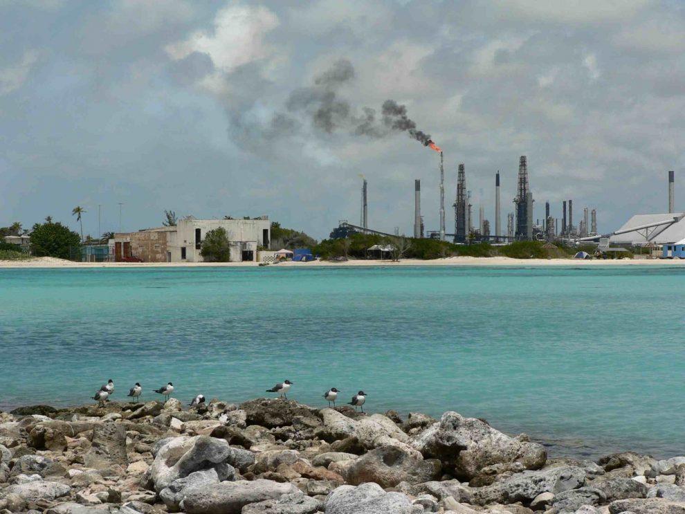 Valero Ölraffiniere von einem Karibikstrand aus fotografiert Kontrast Energieerzeugung Tourismus